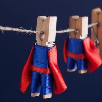 Super team concept photo with clothespin superheroes in blue suit and red cape. Big small powerful heroes. Dark background. soft focus. macro view, shallow depth of field
